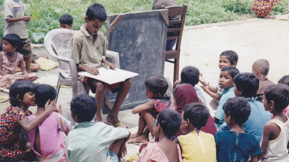 This photo dating to 2002 shows 9-year-old Babar Ali (seated in the chair) teaching ragpickers how to read and write in the backyard of his home in Murshidabad, West Bengal