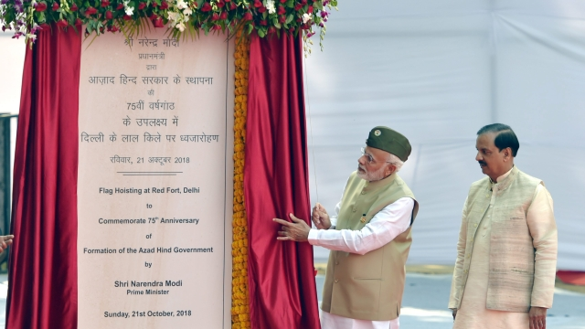 Prime Minister Narendra Modi unveils a plaque as Minister of State (Independent Charge) for Culture and Tourism Mahesh Sharma looks on, to commemorate the flag-hoisting event to mark the 75th anniversary of the 'Azad Hind government' headed by Subhas Chandra Bose, at Red Fort in New Delhi, Sunday, Oct 21, 2018.