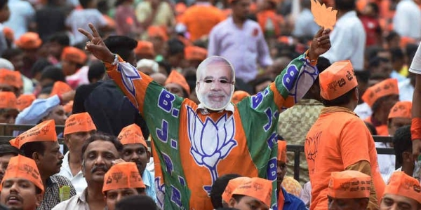 A BJP supporter donning a mask of Prime Minister NarendraModi during a public rally.