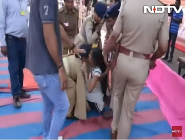 A screengrab showing police personnel forcibly evict Rupal Tadvi from Chief Minister's rally.