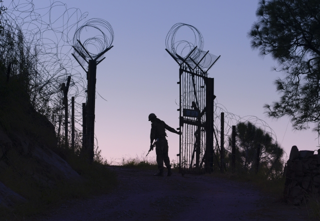 An Indian Army soldier closes the gates on the fence near the Line of Control separating India and Pakistan  in Barasingha area near Bhimber Gali in Poonch sector.