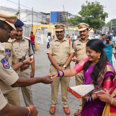 Women distributing sweets to policemen in Hydeabad after the encounter killing of all the four rape-and-murder accused of a vet.