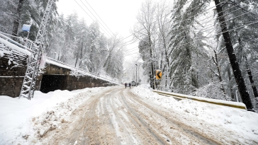 People walk on a snow-covered road during heavy snowfall in Murree, some 60 kilometers north of Islamabad (IANS Photo)