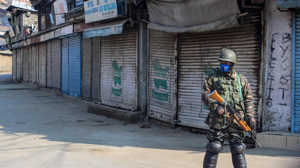 A security personnel stands guard at a closed market, in Srinagar (PTI Photo)