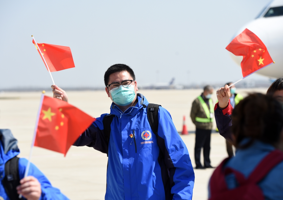Medics, who helped handle the coronavirus crisis in the worst-hit Hubei Province of China, waving to greeters on their return to Hefei in east China on March 18, 2020. Medical assistance teams have started leaving Hubei Province as the epidemic appears to have been subdued.