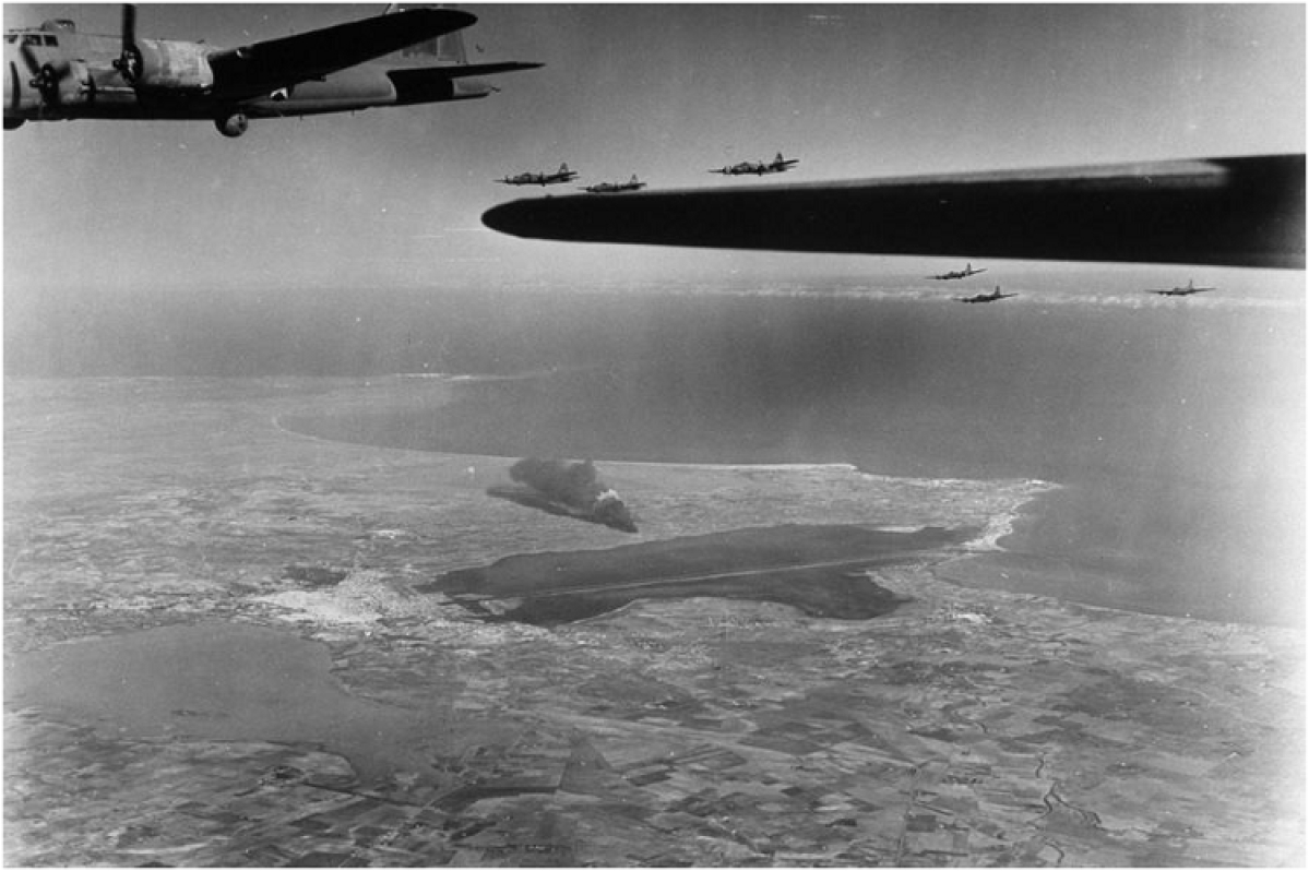 Twelfth U.S. Air Force in B-17 bombers fly over the African coast returning from a bombing mission near El Aouina airfield in 1943, during World War II. By using a silhouette of a bomber wing against an otherwise light greyish scene the viewers' attention goes there first. The group of bombers surround the wing at a distance and another bomber is in proper view close by thereby conveying what's happening in the scene. The aerial view of the sea and coastline gives a sense of location for the photo.