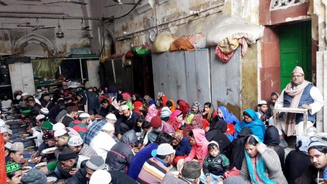 لنگر کا انتظام و انصرام کی ذمہ داری سنبھالنے والے سید خسرو نظامی (دائیں جانب کرسی پر بیٹھے ہوئے) اور لنگر کھاتے ہوئے درگاہ میں موجود زائرین