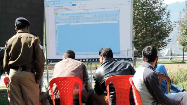 جموں و کشمیر بلدیاتی انتخابات کے نتائج بڑی اسکرین پر دیکھتے ہوئے لوگ