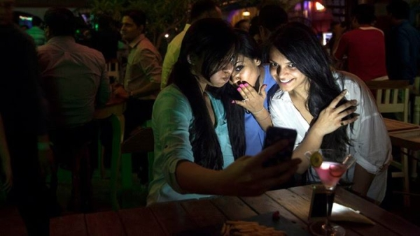 'ट्रूली मैडली' द्वारा आयोजित पार्टी में सेल्फी लेती युवतियाँ (फोटो : एपी)