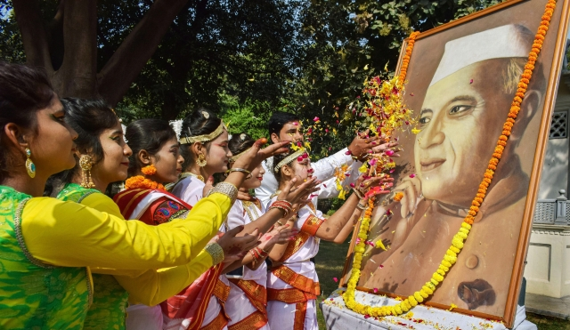 इलाहाबाद में पंडित जवाहर लाल नेहरू की 129वीं जयंती पर उनकी तस्वीर पर पुष्प अर्पित करते स्कूली बच्चे (फोटो- 14 नवंबर)