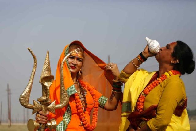 20 नवंबर, मंगलवार को इलाहाबाद में कुंभ मेले से पहले  भारतीय ट्रांसजेंडर संतों  की गुरू भवानी मां (बाएं) एक त्रिशूल धारण करते हुए तो वहीं दूसरा ट्रांसजेंडर शंख बजाते हुए.