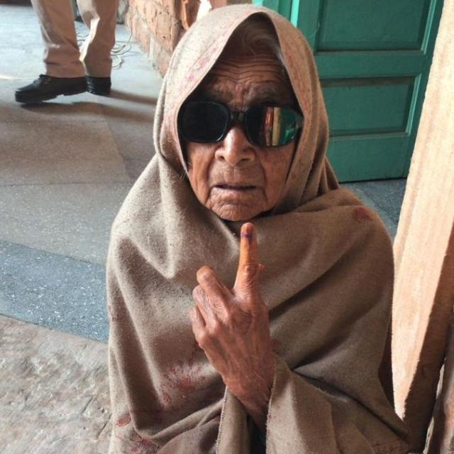 वोट डालने के बाद 80 साल की महिला स्याही का निशान दिखाती हुईं