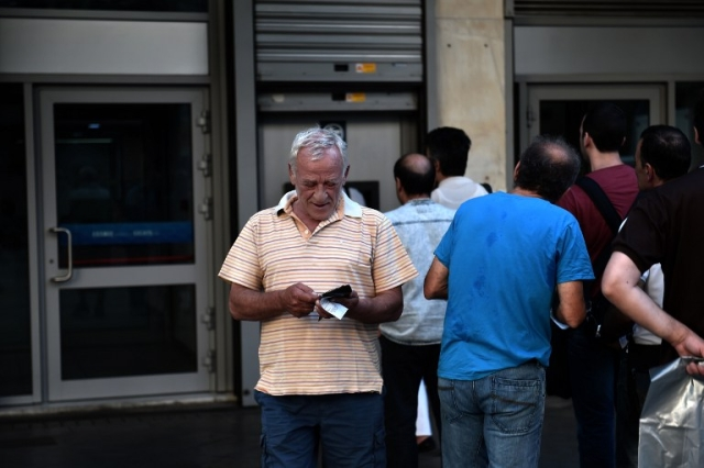 People queue outside a bank to withdraw cash from an ATM in Athens on July 7, 2015. AFP PHOTO / ARIS MESSINIS
