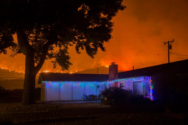 Christmas decorations illuminate a house as the growing Thomas Fire advances toward Santa Barbara County seaside communities in Carpinteria, California. (David McNew/Getty Images)