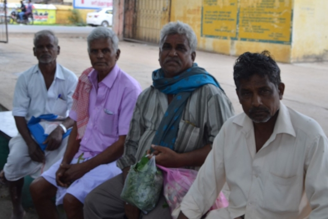 Chandrasekar, second from right, waits with his fellow farmers for his payment at the Vellore regulated market.
