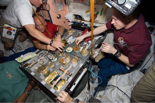 Crew members gather for a meal at the galley in the Unity node of the International Space Station. (Wikimedia Commons)