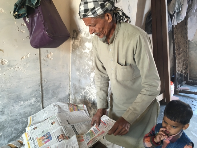 Akhtar Ali alias Dharam Singh goes through newspaper reports about his son's case.