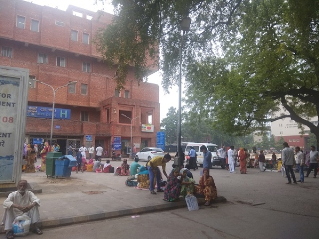 People wait to be attended to outside another government hospital in Delhi.