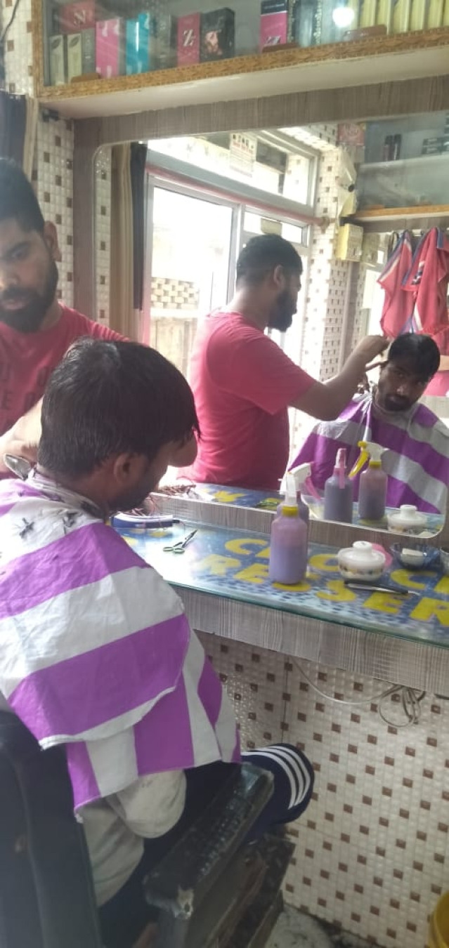 Riyaz Alam giving haircut to a customer from Valmiki community