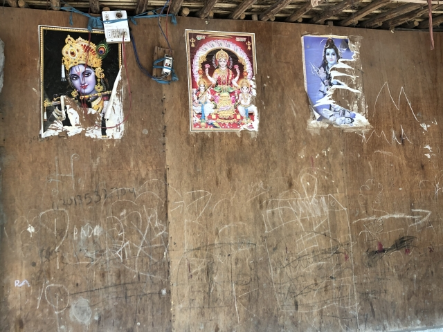 Pictures of gods and goddesses stuck on the wall of a house.