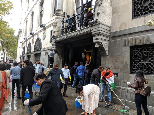 Diaspora volunteers wash the floors outside the high commission.
