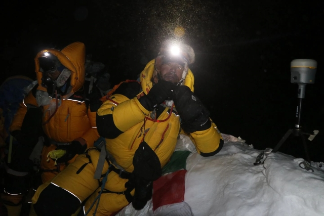 Nepali surveyor Khim Lal Gautam (right) at the summit of Mount Everest in the early hours of 22 May. On his left is a satellite navigation device to measure the mountain's peak.