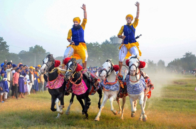 Men of the armed Sikh order Nihang show their horse-riding skills during a religious procession on 'Fateh Divas', or 'Victory Day', in Amritsar on Monday (28 October 2019). PTI