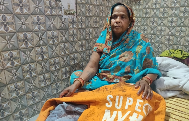 Shakuntala, mother of Lala, shows his blood-soaked sweat-shirt