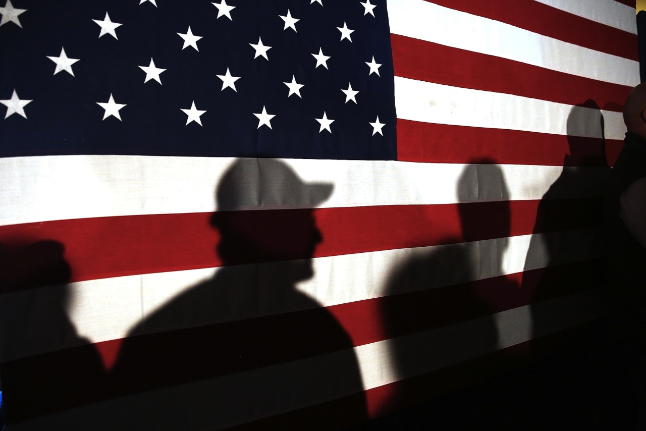 MYRTLE BEACH, SC - FEBRUARY 11:  Shadows are reflected on an American Flag as people line up to speak with Ohio Governor and Republican presidential candidate John Kasich at a restaurant in South Carolina following his second place showing in the New Hampshire primary on February 11, 2016 in Myrtle Beach South Carolina.  Kasich, who is running as a moderate, is expected to face a difficult environment in South Carolina where conservative voters traditionally outnumber moderates.  (Photo by Spencer Platt/Getty Images)