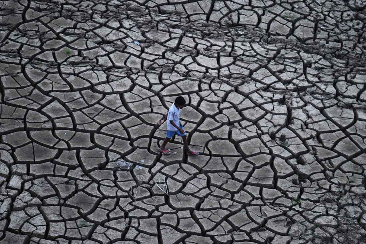 An Indian farmer walks on dry land in a drought-hit area. (Sanjay Kanojia/AFP/Getty Images)