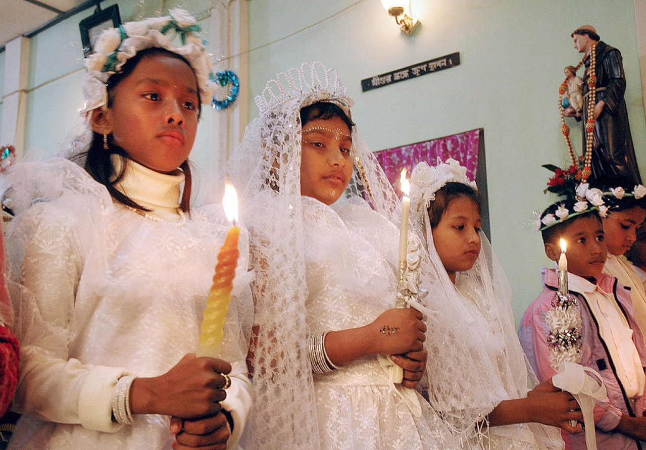 Indian children hold candles as they stand ahead of their first communion during the celebrations of Christmas at a church in Agartala, capital of India's northeastern state of Tripura, early 25 December 2006. Although Christians make up less than 3 percent of the country's one-billion-plus population, Christmas is widely celebrated in India. AFP PHOTO (Photo credit: STRDEL/AFP/Getty Images)