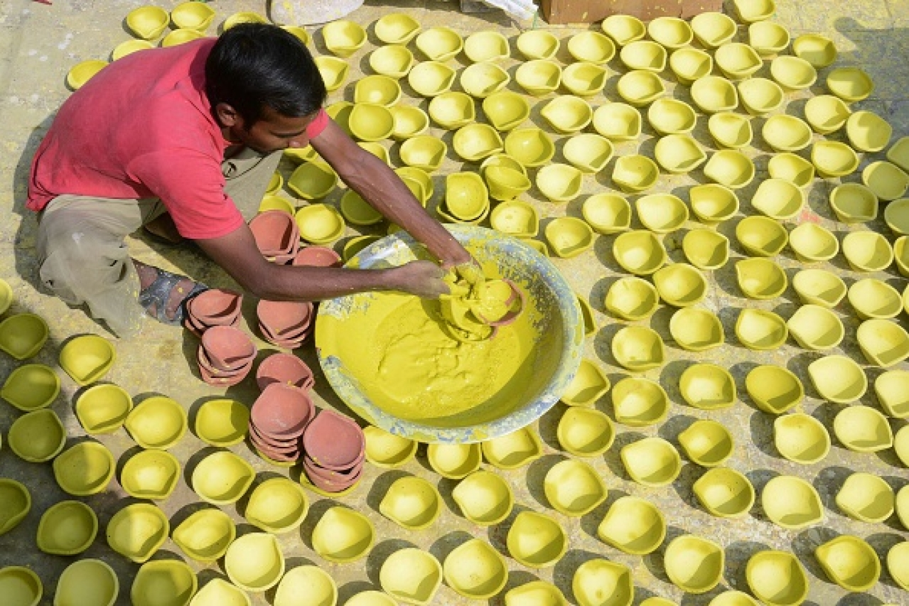A craftsman paints diyas  in Amritsar.