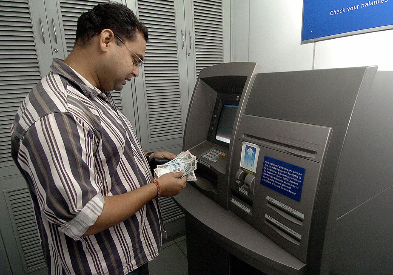 A bank customer withdraws money from an ATM counter in New Delhi. Photo credit: PRAKASH SINGH/AFP/GettyImages