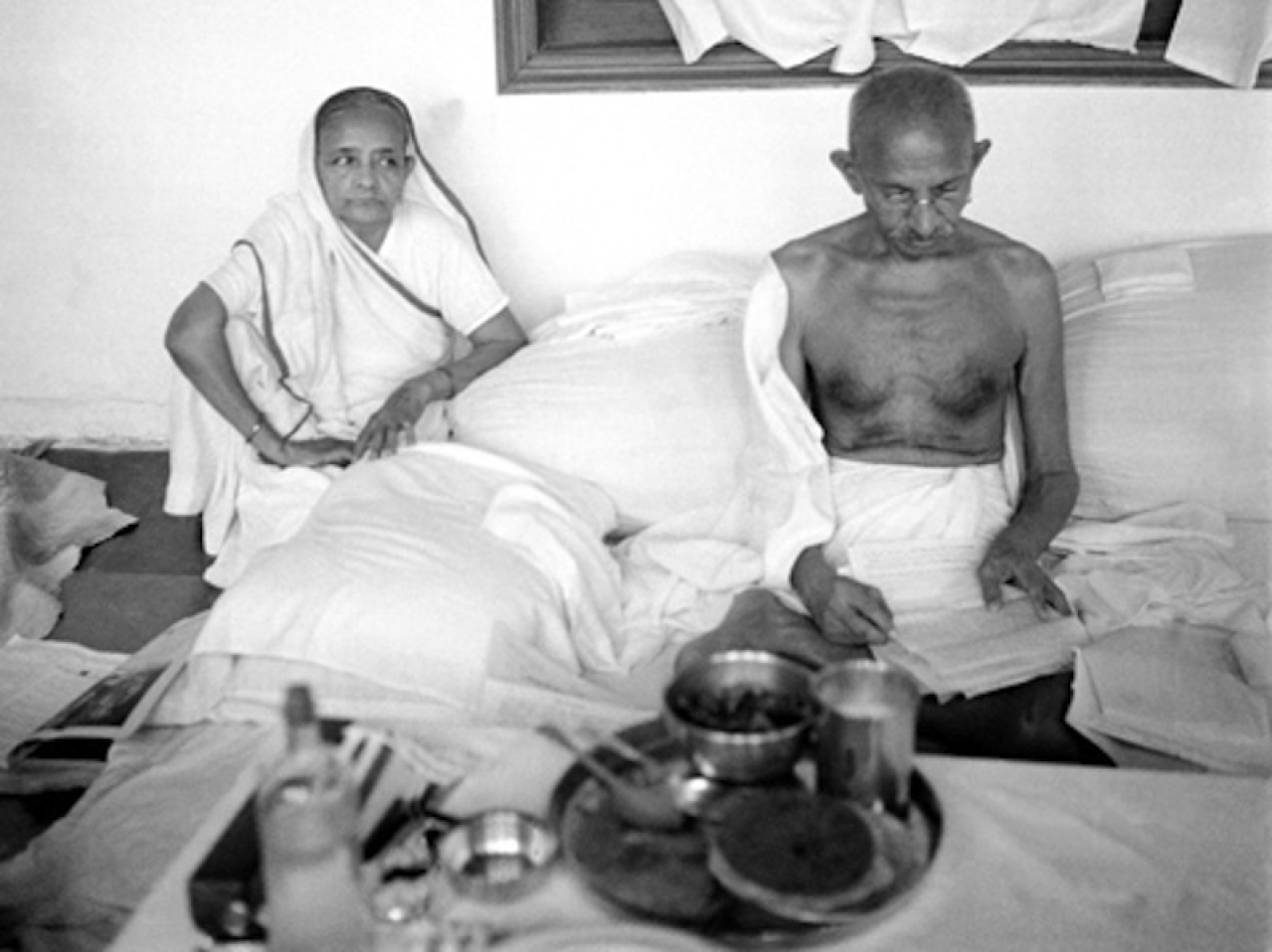 Kasturba watches as Gandhi reads