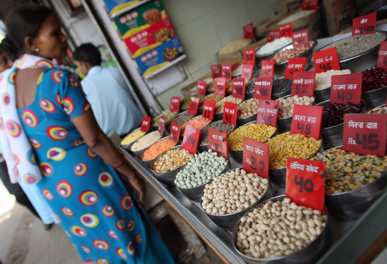 An Indian woman checks the price of pulses and grains at a  wholesale market in New Delhi. (Photo Credit: MANAN VATSYAYANA/AFP/Getty Images)