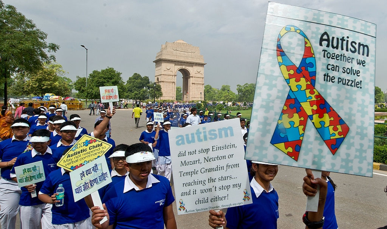 School children carry placards as they participate in the Autism Awareness Walk 2013.