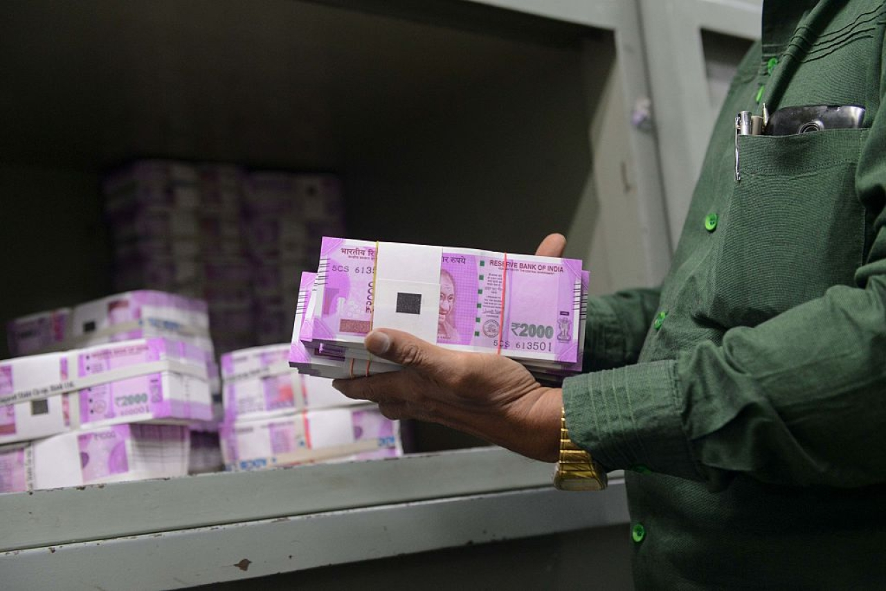 An Indian bank employee checks stacks of new 2,000 rupee notes in Ahmedabad. Photo credit: SAM PANTHAKY/AFP/GettyImages