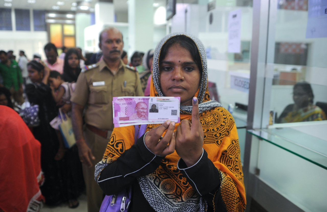 A Indian woman poses with new 2000 rupee notes. (ARUN SANKAR/AFP/Getty Images)