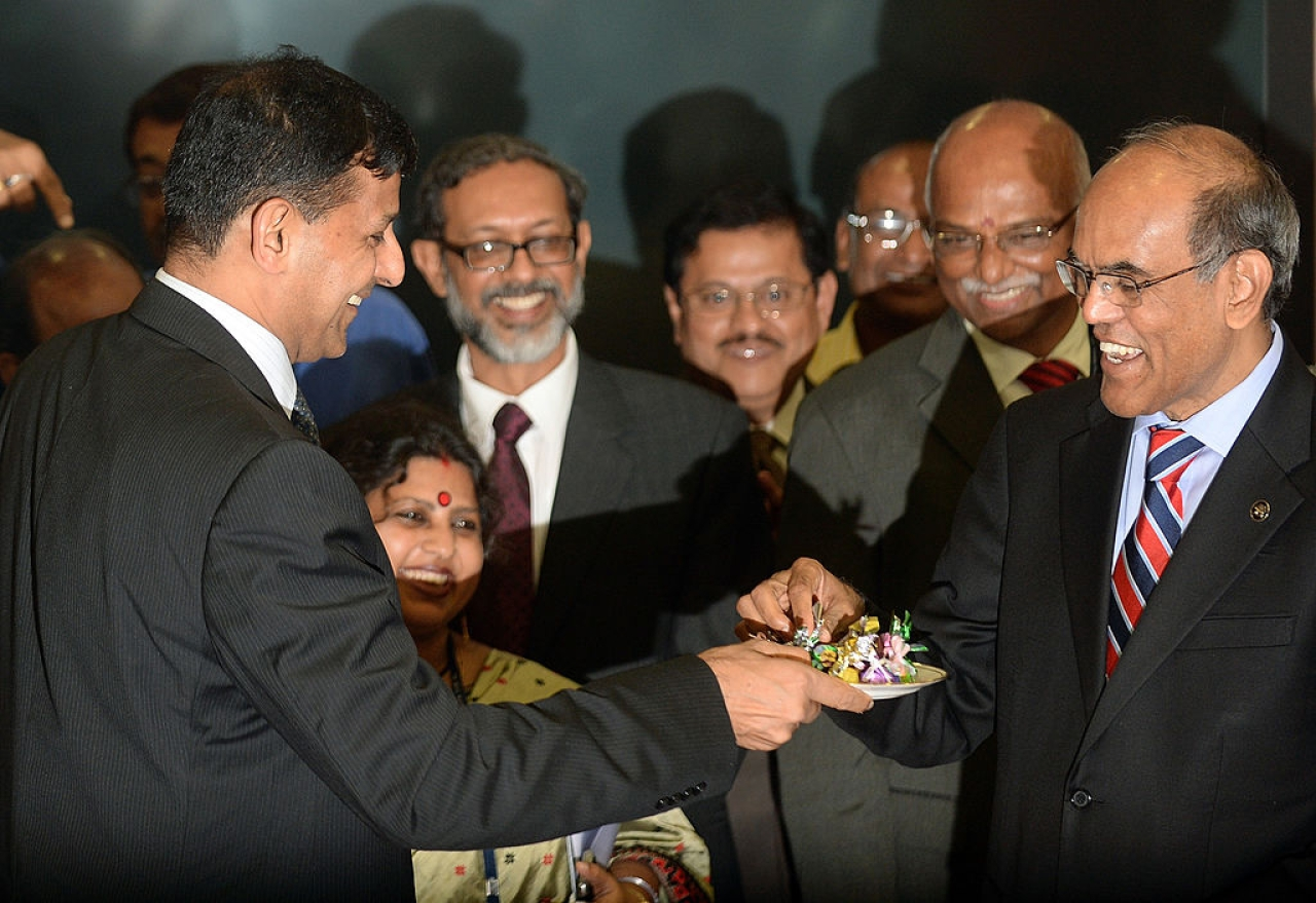 Reserve Bank of India's (RBI) newly appointed governor Raghuram Rajan (L) offers sweets to outgoing governor Duvvuri Subbarao (R) during the hand over ceremony at the RBI headquarters in Mumbai on September 4, 2013. Top economist Raghuram Rajan, renowned for predicting the 2008 global financial crisis, takes over as head of India's central bank on September 4, amid the country's worst financial storm in years. AFP PHOTO/ PUNIT PARANJPE (Photo credit should read PUNIT PARANJPE/AFP/Getty Images)