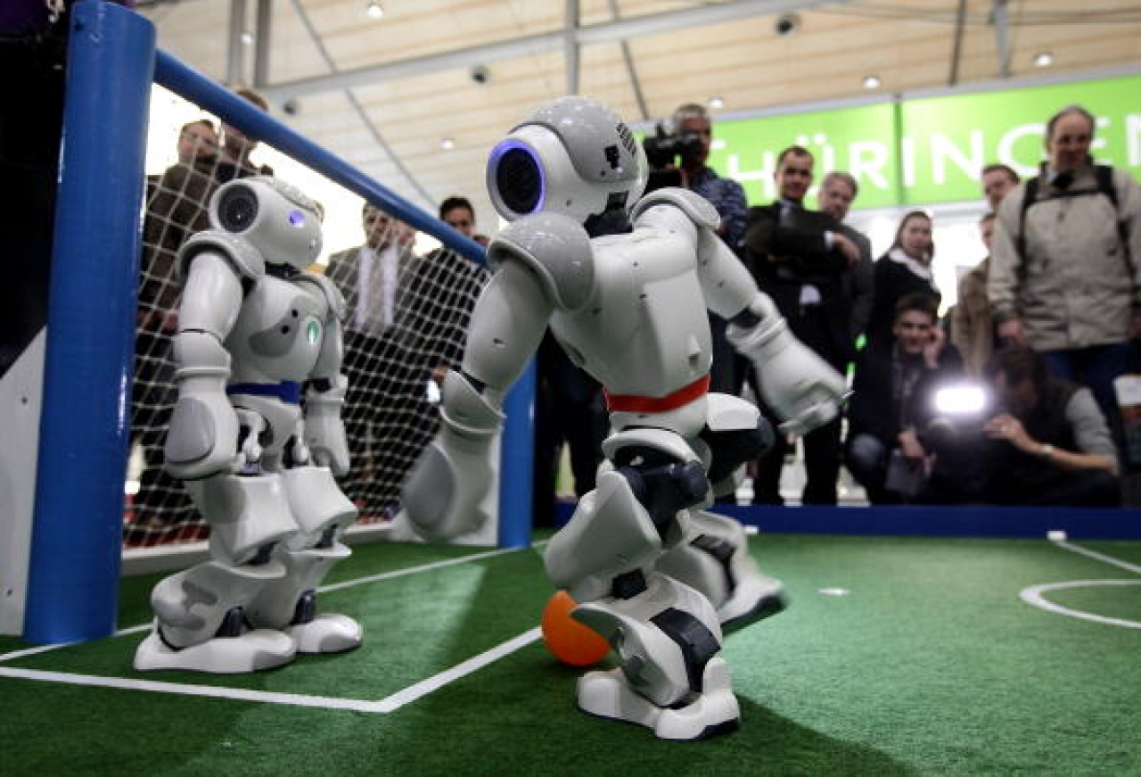 Robots play football in a demonstration of artificial intelligence at the stand of the German Research Center for Artificial Intelligence. (Photo by Sean Gallup/GettyImages)