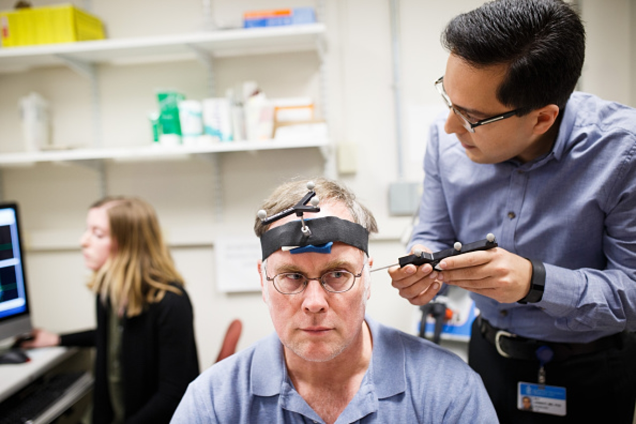 Research fellow Ali Jannati simulates a TMS therapy session on John Elder Robison as he sits in the room where he took part in brain therapy known as TSM (Transcranial magnetic stimulation) at Beth Israel Hospital in Boston, Mass. (Keith Bedford/The Boston Globe via Getty Images)