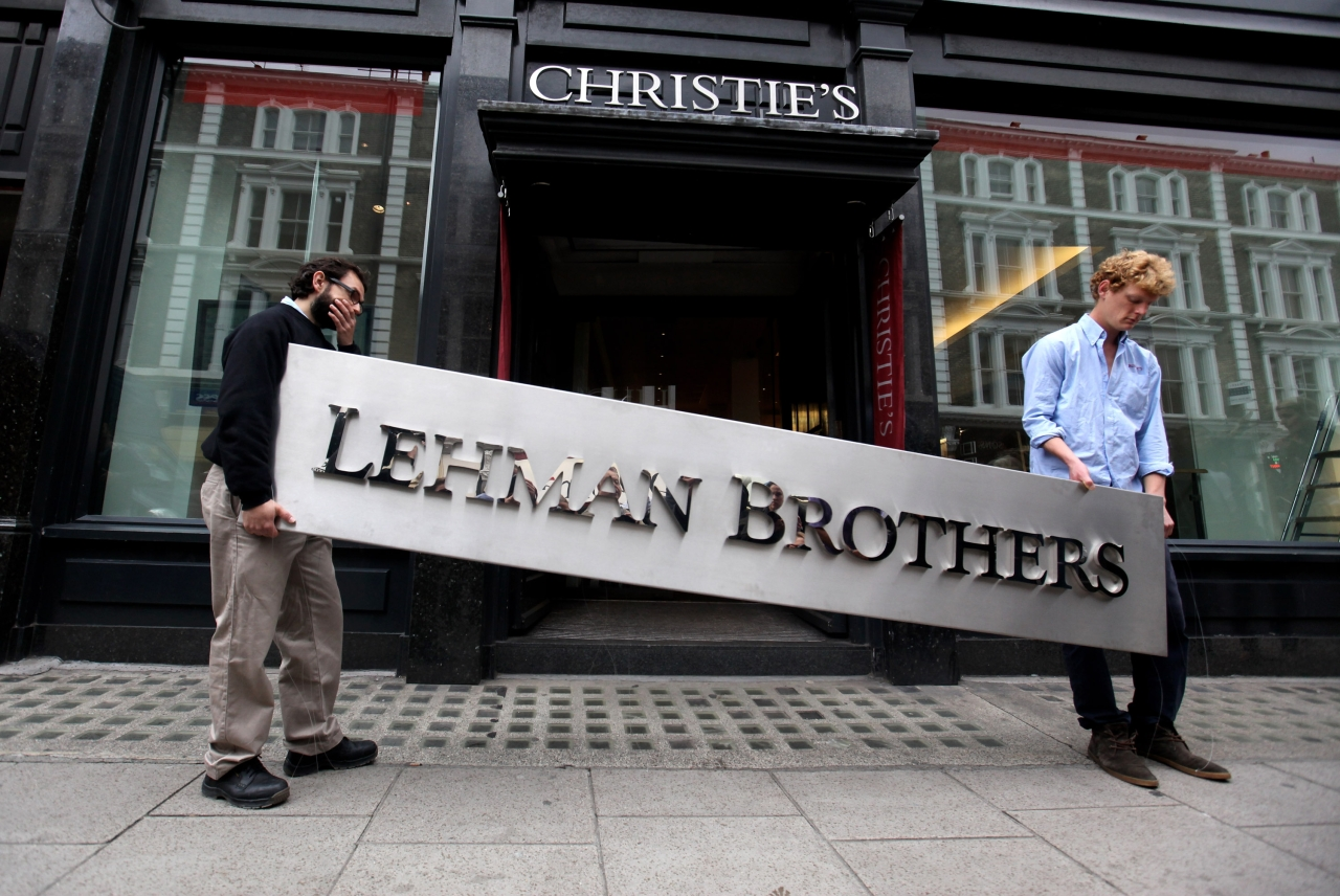 Two employees of Christie's auction house manoeuvre the Lehman Brothers corporate logo, which is estimated to sell for 3000 GBP and is featured in the sale of art owned by the collapsed investment bank Lehman Brothers on September 24, 2010 in London, England. (Oli Scarff/Getty Images)