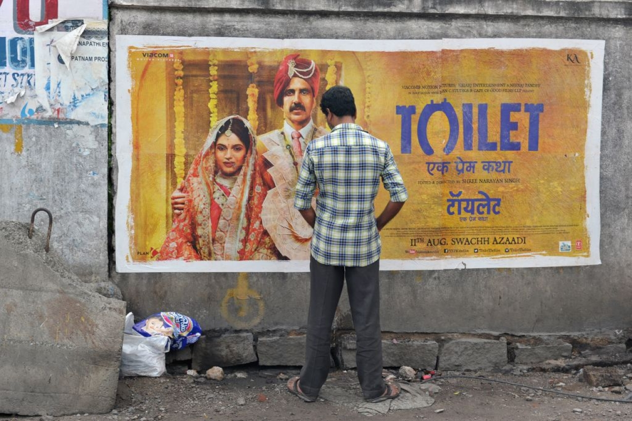 An Indian man urinates on a wall on the roadside in front of a poster for the Hindi film 'Toilet' in Hyderabad on August 12, 2017. The Bollywood film 'Toilet: Ek Prem Katha' ('Toilet: A love story'), which was released on August 11, is inspired by the true-life tale of one man's battle to build toilets in his village in rural India. / AFP PHOTO / NOAH SEELAM (Photo credit should read NOAH SEELAM/AFP/Getty Images)