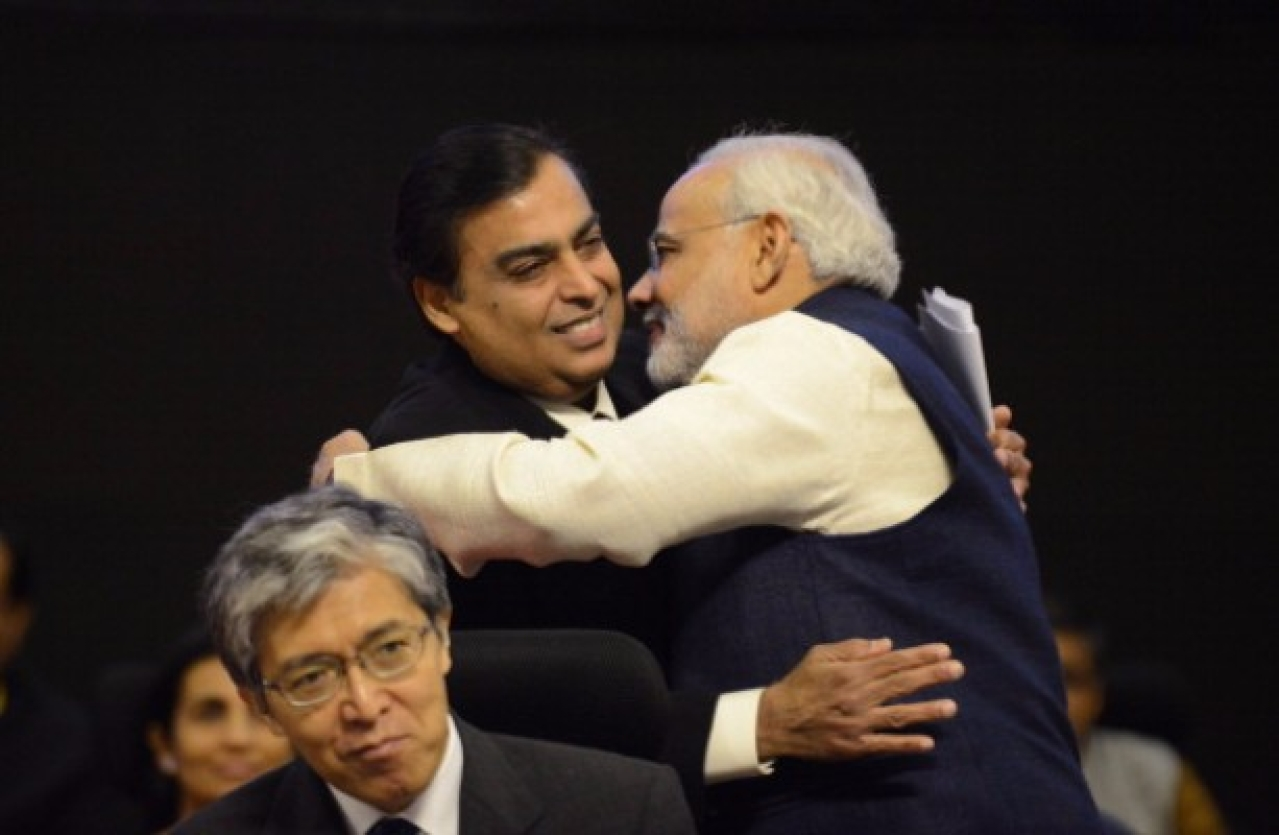 Narendra Modi (R) greets Reliance chairman and managing director Mukesh Ambani. (SAM PANTHAKY/AFP/Getty Images)