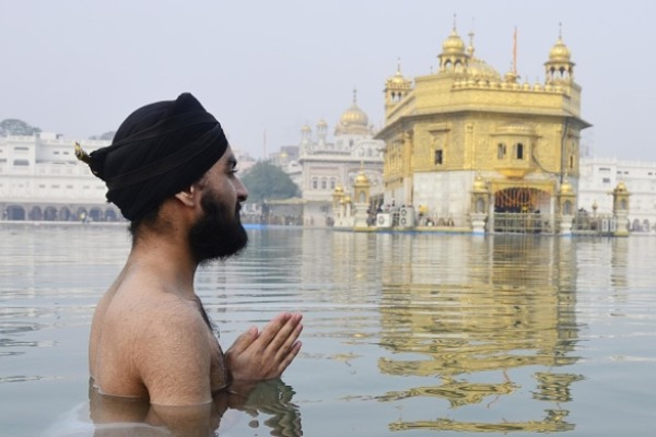 A Sikh devotee takes bath in the holy sarovar and pays obeisance at Golden Temple in Amritsar. (Sameer Sehgal/Hindustan Times via Getty Images)
