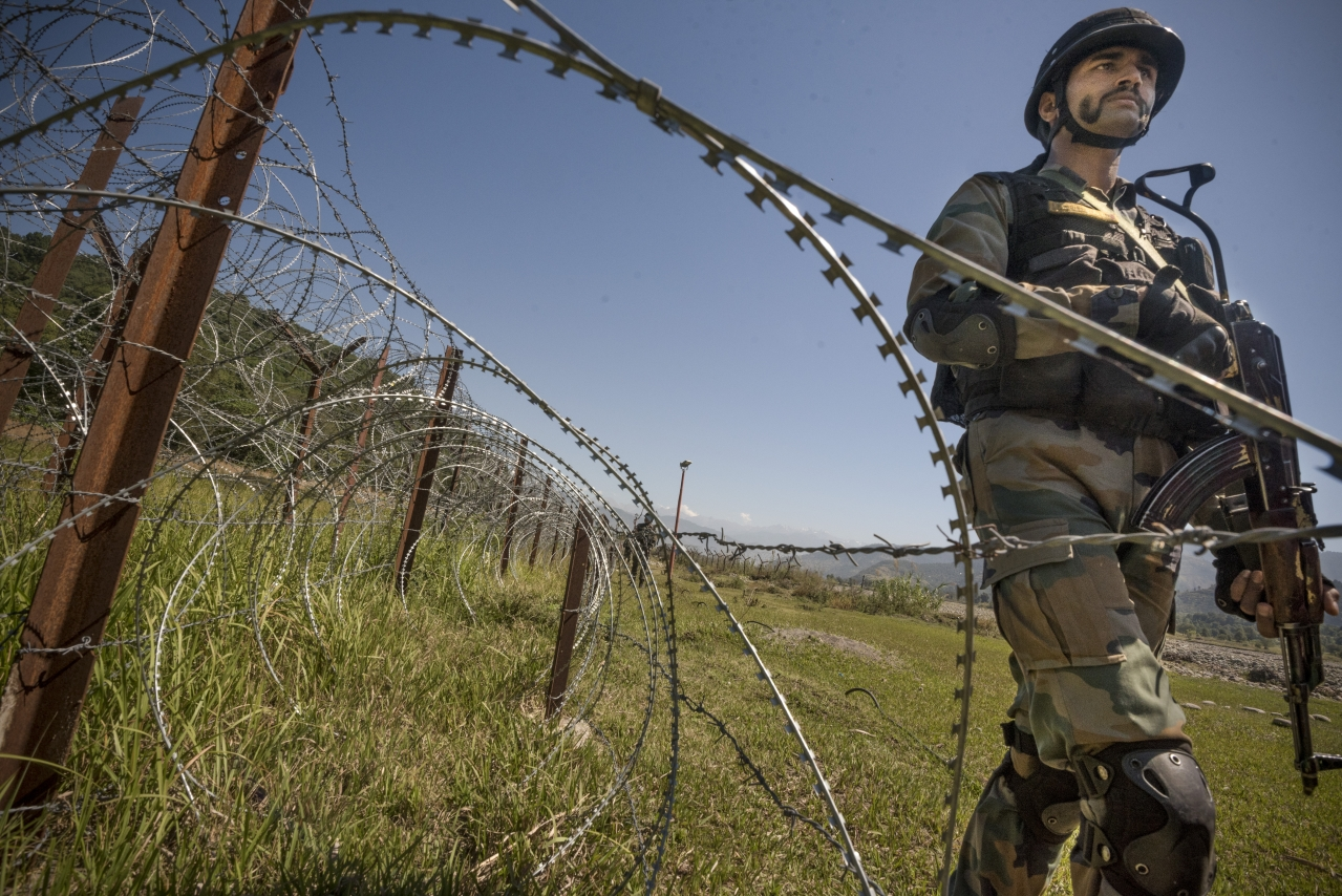 An Indian Army soldier patrols on the fence near the India-Pakistan LOC. (Gurinder Osan/Hindustan Times via Getty Images)