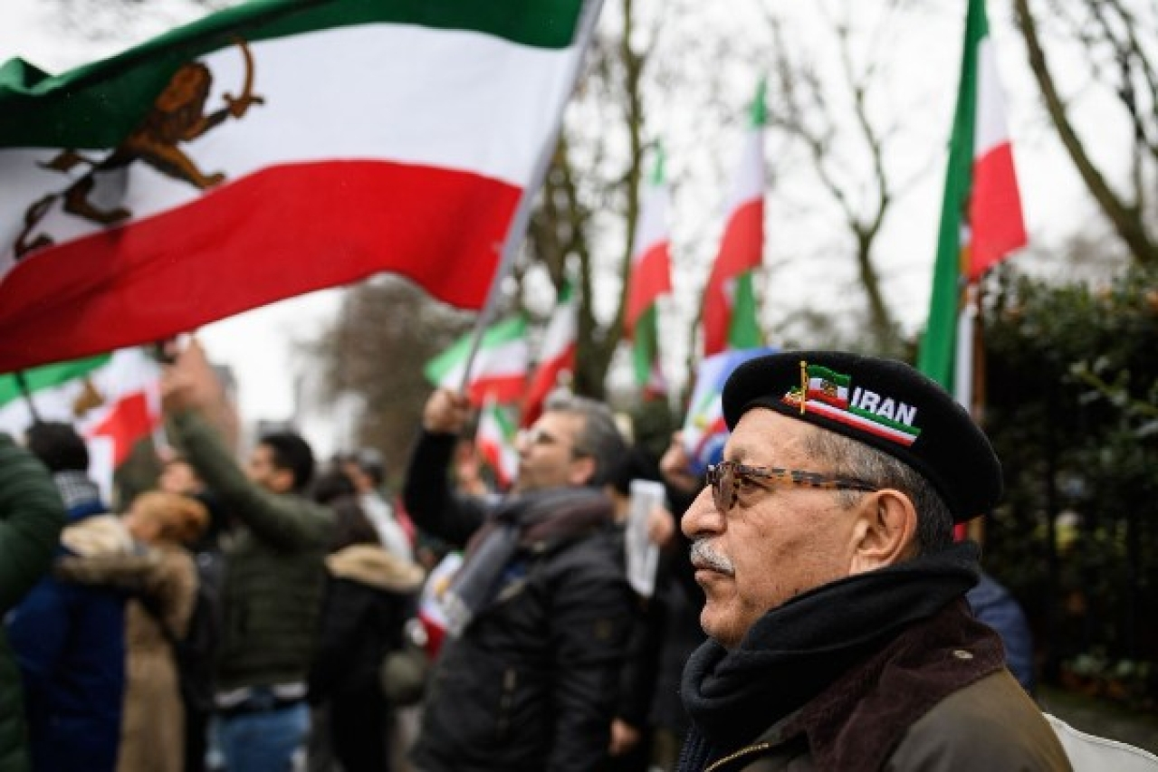 A man wearing an Iran beret stands with anti-regime protesters as they demonstrate outside the Iranian embassy in London, England. (Leon Neal/Getty Images)