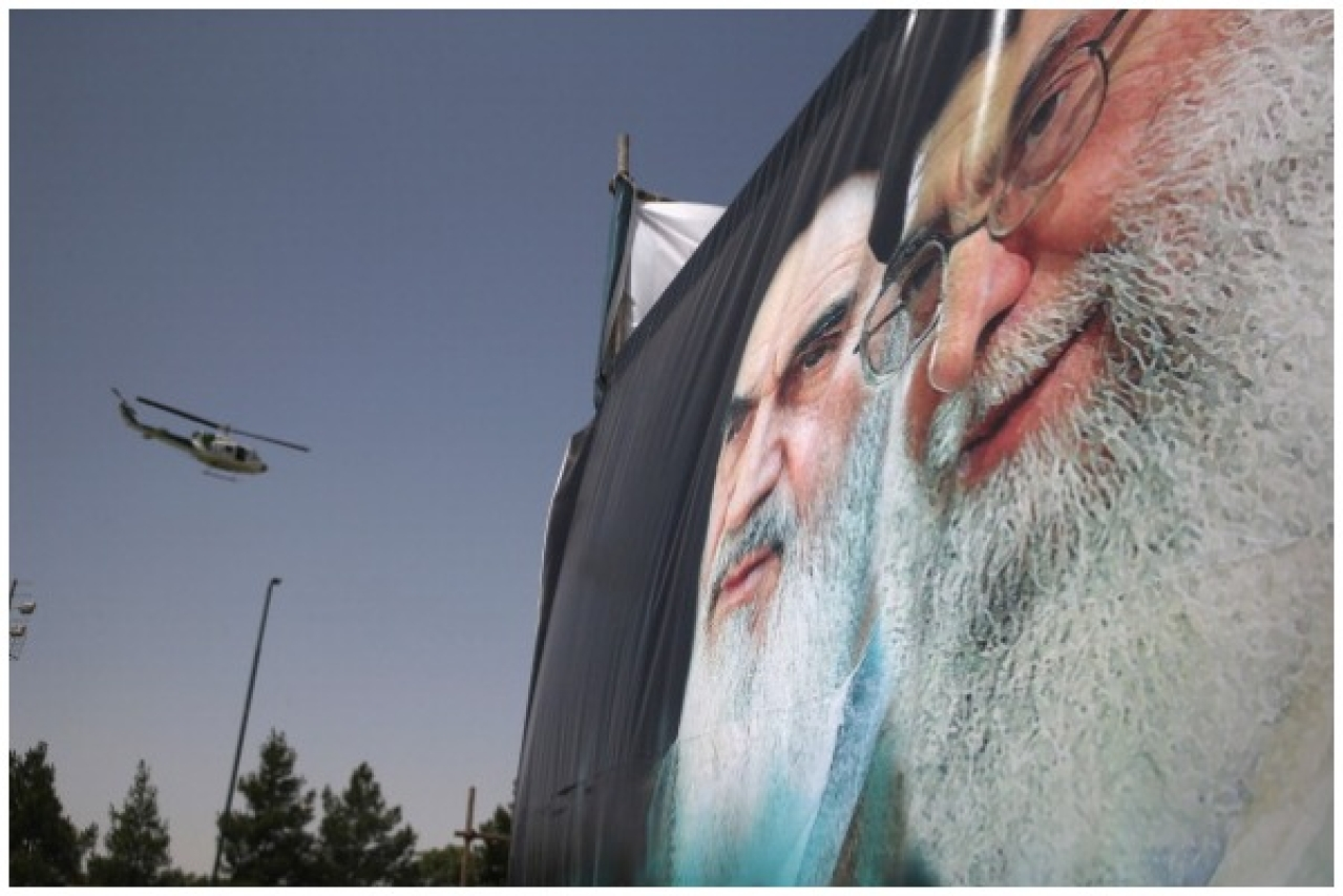 An Iranian police helicopter passes above portraits of Iran's supreme leader Ayatollah Ali Khamenei (R) and the former Ayatollah Khomeini outside Khomeini's shrine on the 25th anniversary of his death on June 4, 2014 (John Moore/Getty Images)