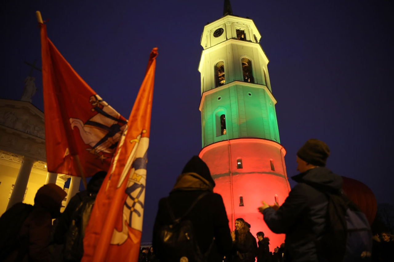 People dance next to the bell tower of Vilnius Cathedral as it stands illuminated in the colours of the Lithuanian flag to mark the 100th anniversary of the restoration of Lithuanian statehood in Vilnius, Lithuania. (Sean Gallup/Getty Images)