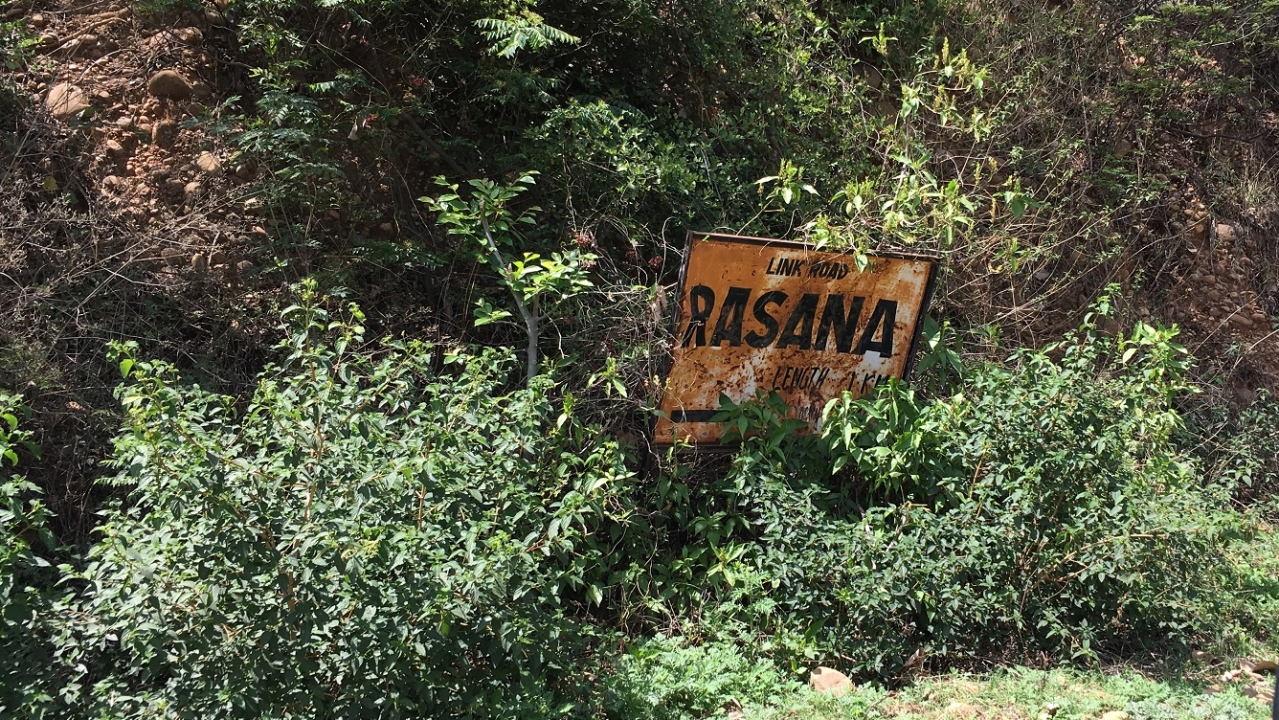 A battered iron board  announces the entry to Patta Rasana village